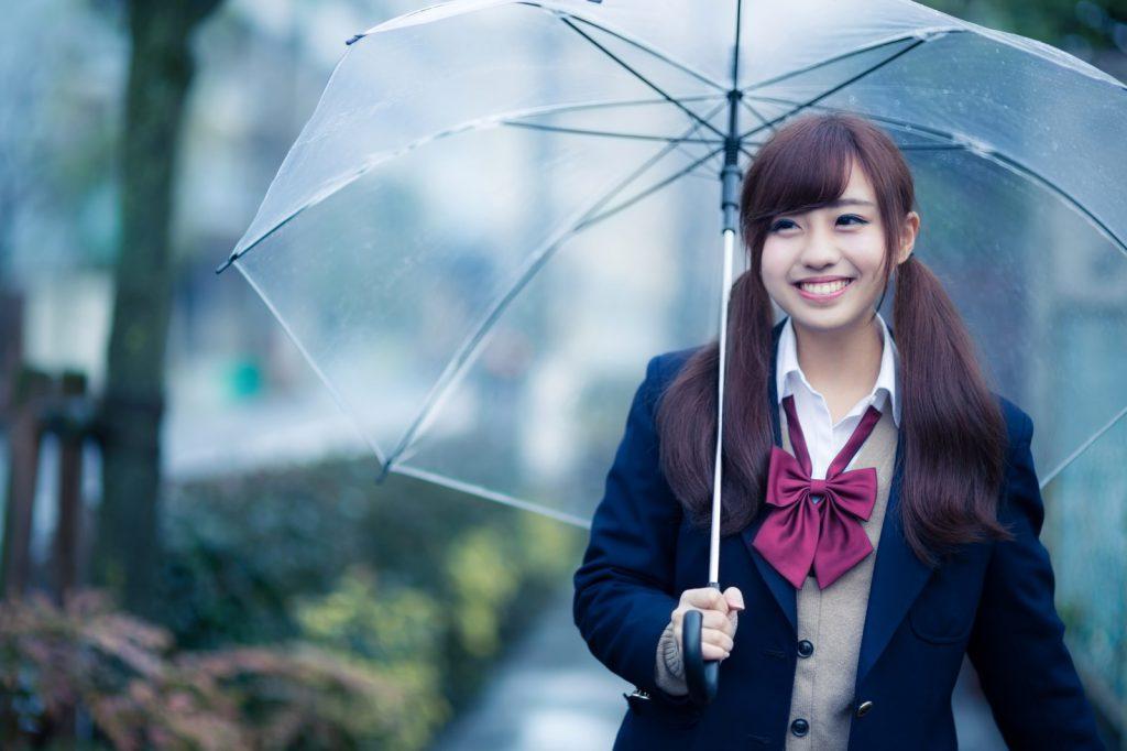 傘をさす笑顔の女子高生